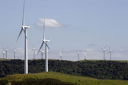 Wind turbines on top of green hills Stock Photo
