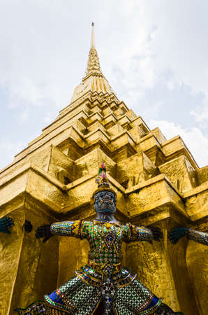 The demon statue supporting golden pagoda at Wat Phra Kaew  Temple of the Emerald Buddha , Bangkok , Thailand photo
