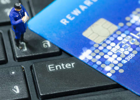 miniature policeman standing on the keyboard with credit card photo