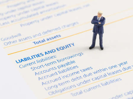 miniature businessman stand on the balance sheet photo