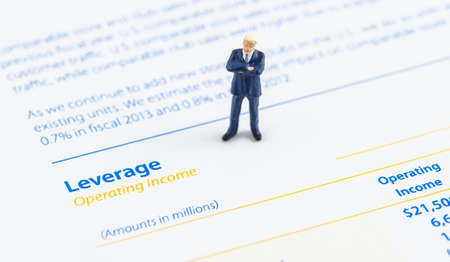miniature businessman stand on the financial statement photo