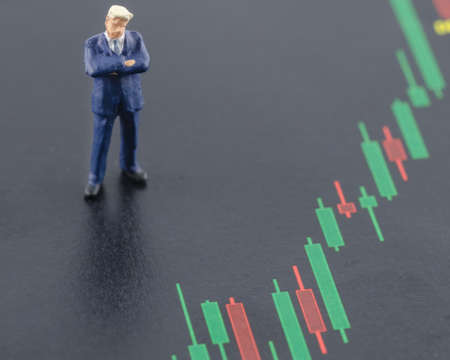 miniature business man standing on the candlestick stock chart Zdjęcie Seryjne
