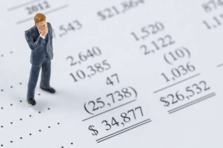 miniature people: miniature businessman standing on the bottom line Stock Photo