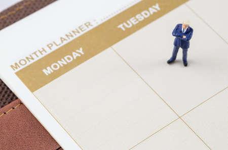 almanac: miniature businessman standing on the planner book