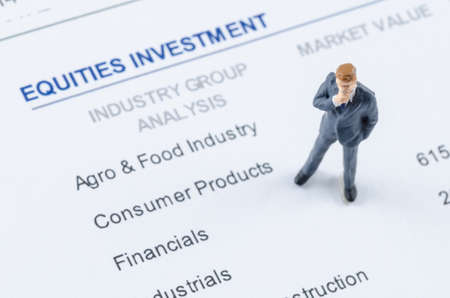 allocate: miniature businessman standing on the portfolio investment