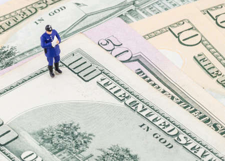 miniature policeman standing on the US dollar banknote photo
