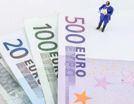 miniature policeman standing on the Euro banknote photo