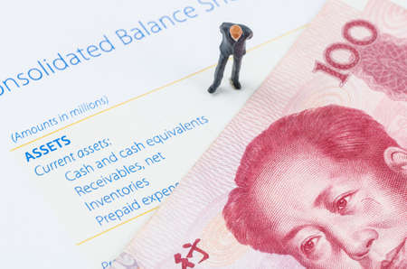 miniature businessman standing with Chinese banknote on the balance sheet photo