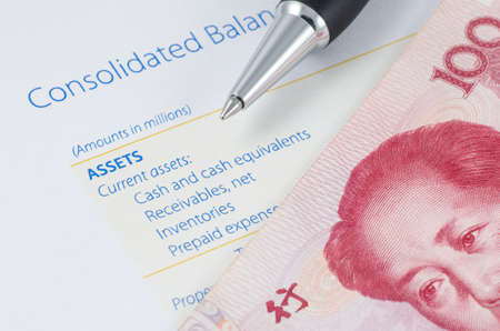 pen with Chinese banknote on the balance sheet photo