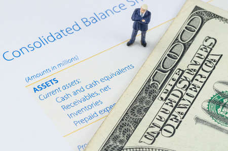 miniature businessman standing with US dollar banknote on the balance sheet photo