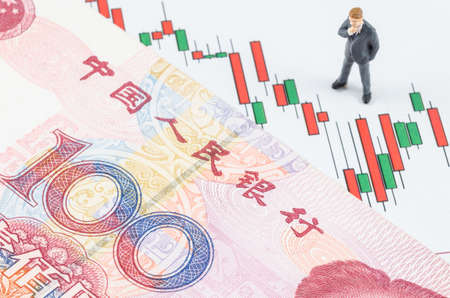 economic growth: miniature businessman standing with Chinese banknote on the candlestick stock chart