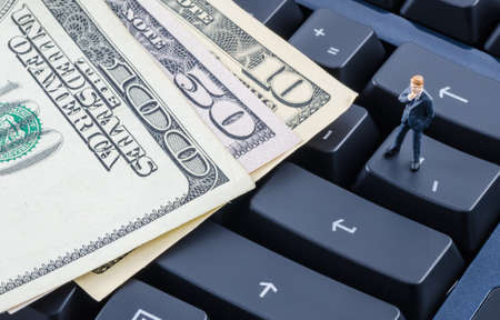 e cash: miniature businessman standing on the computer keyboard with credit card and US dollar banknote