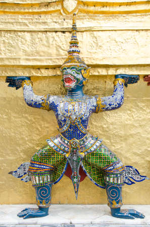 The demon statue supporting golden pagoda at Temple photo