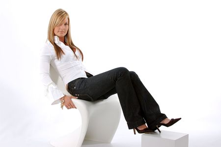 Young woman sitting on a white chair photo