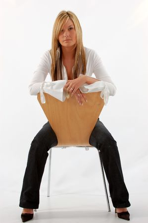 Young woman sitting on a wooden chair photo
