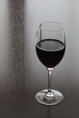 Glass of red wine on a wooden table Stock Photo