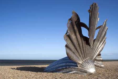 Scallop Sculpture by Maggie Hambling on Aldeburgh Beach, Suffolk, England.  The work is a tribute to the composer Benjamin Britten and is inscribed with the words I hear the voices that will not be drowned, from the opera Peter Grimes.