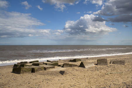 Rain clouds passing over concrete blocks on  Benacre Beach in Suffolk Stock Photo - 14387131
