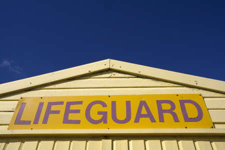 Yellow lifeguard sign, on yellow lifeguard hut, isolated against a blue sky.
