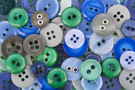Closeup image of green and blue sewing buttons
