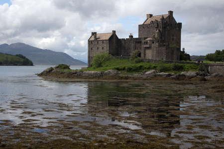 Eilean Donan Castle in Scotland, against a cloudy sky