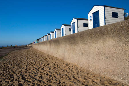 Blue and white beach huts against a blue sky at Southwold, Suffolk , England photo