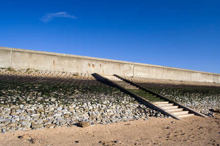 Sea wall and steps leading down to the beach on Canvey Island, Essex, England