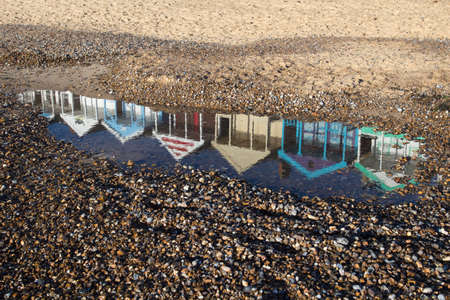 Reflections of beach huts in a puddle on Southwold beach, Suffolk, England photo