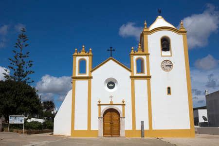 Church of Nossa Senhora da Luz, Praia da Luz, Algarve, Portugal, against a blue sky