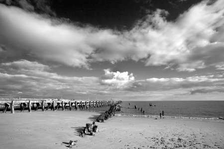 groyne: Black and white image of the harbour wall and groyne on Walberswick beach Suffolk, England