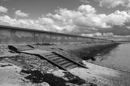 Black and white image of the sea wall and steps leading down to the beach at Thorney Bay, Canvey Island, Essex, England