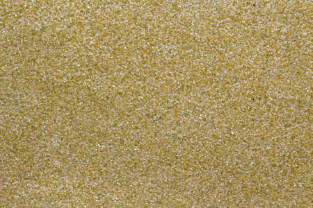 sandpaper: Closeup image showing the texture of a coarse yellow sandpaper