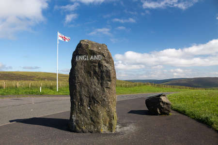 English flag, rock with England painted on it and information board marking the Scottish - English Border, Northumberland, United Kingdom