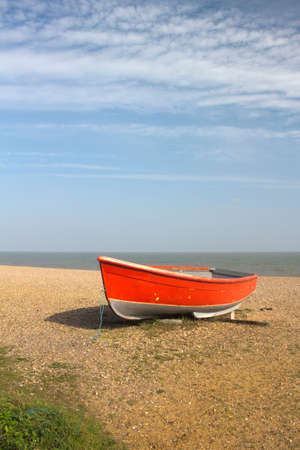Red fishing boat on Dunwich Beach in Suffolk, England