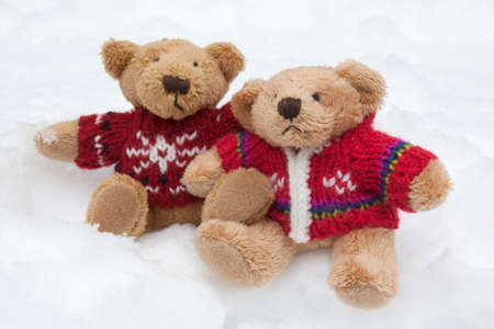 Teddy bears with colourful knitted jumpers (Christmas tree decorations) in the snow Stock Photo
