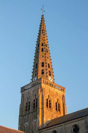 Catholic church in Bollezeele, France, against a blue sky.