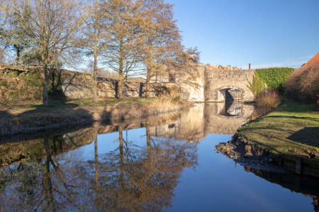Reflections of the ramparts and trees in Bergues, northern France, against a blue sky.