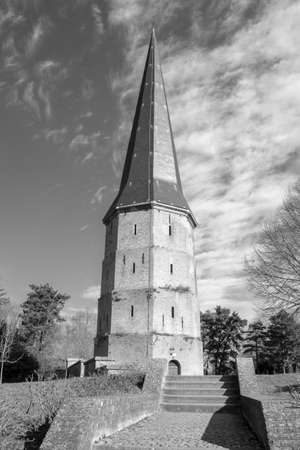 Black and white image of the pointed tower of Saint Winoc Abbey, Bergues, France