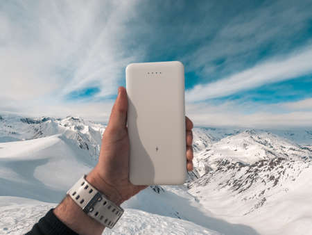 Power bank in hands. Tourist charges a devices in nature, against the backdrop of a winter mountains landscape Archivio Fotografico