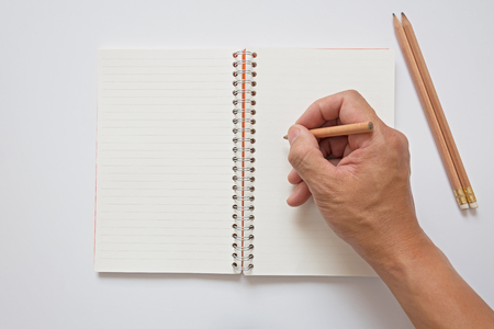hand lay: open note book lay on white background and  hand hold pencil Stock Photo