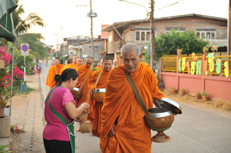 alms: chaingkhan in loie province, Thailand - november 17 :street life in chaingkhan in loie province on november17, 2015. give alms to a Buddhist monk sticky rice