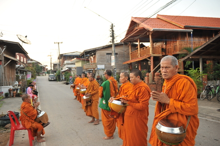 limosna: chaingkhan in loie province, Thailand - november 17 :street life in chaingkhan in loie province on november17, 2015. give alms to a Buddhist monk sticky rice