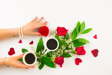 heartshaped: Marriage proposal with pearl ring in man hand, red roses and woman hand with coffee Stock Photo