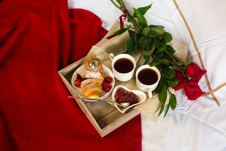 Valentines day table setting with plate, gift, red ribbon and roses. background Stock Photo