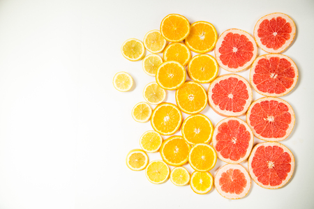 Gradient citrus slices - grapefruit, orange and lemon, placed on white background from left to right, from big to smaller sizes