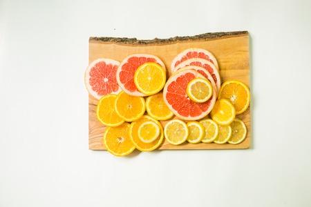 flesh colour: Vitamin C fruits - lemon, orange and grapefruits slices on woden cutting board on white background