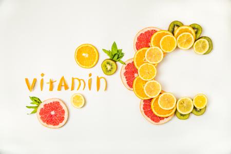 Vitamine C-letters gemaakt van citrusvruchten - citroen, grapefruit, kiwi en stukjes sinaasappel op witte achtergrond