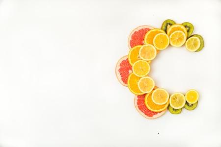 flesh colour: Vitamin C letters made of citrus fruits - lemon, grapefruit, kiwi and orange slices on white background