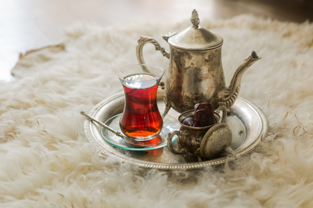 Tea set in oriental style in pear shaped glass with spoon and intage kettle and dates fruit on silver tray on sheep fur rug