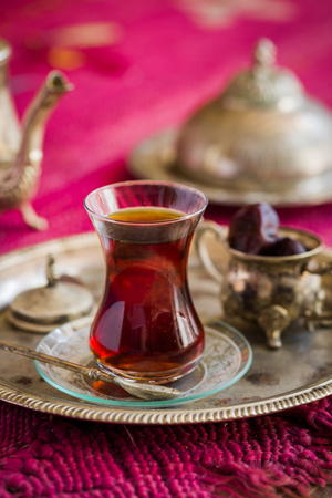 religion ritual: Tea set in oriental style in pear shaped glass with spoon and vintage kettle and dates fruit on silver tray on pink old rug Stock Photo